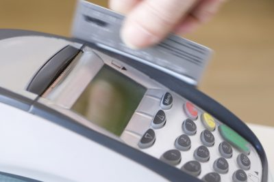 credit card being swiped in credit card machine