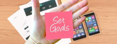 set goals sticky note on a persons hand